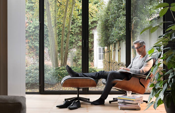 A man is sitting comfortably indoors reading a book as his Daikin units create the perfect climate.